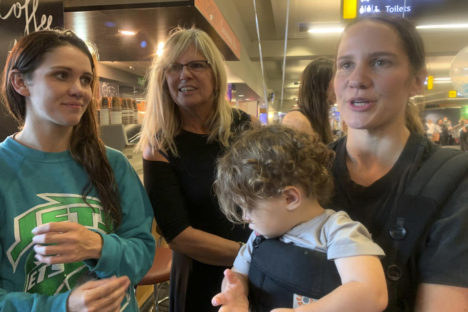 Kristy Mather, right, arrives from Sydney at the Wellington International Airport in Wellington, New Zealand Monday, April 19, 2021. The start of quarantine-free travel was a relief for families who have been separated by the coronavirus pandemic as well as to struggling tourist operators. (AP Photo/Nick Perry)