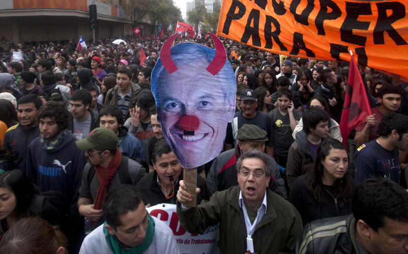 A protester holds up an image mocking Chile's President Sebastian Pineda as demonstrators march toward La Moneda presidential palace on the second day of a national strike in Santiago, Chile, Thursday Aug. 25, 2011.  Chileans marched peacefully Thursday, demanding profound changes in the country's heavily centralized and privatized form of government. Union members, students, government workers and Chile's center-left opposition parties joined the nationwide two-day strike. (AP Photo/Victor R. Caivano)