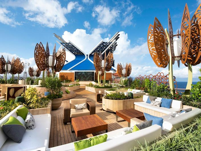 outdoor seating and tables among plants and public art on the rooftop garden of the Celebrity Edge