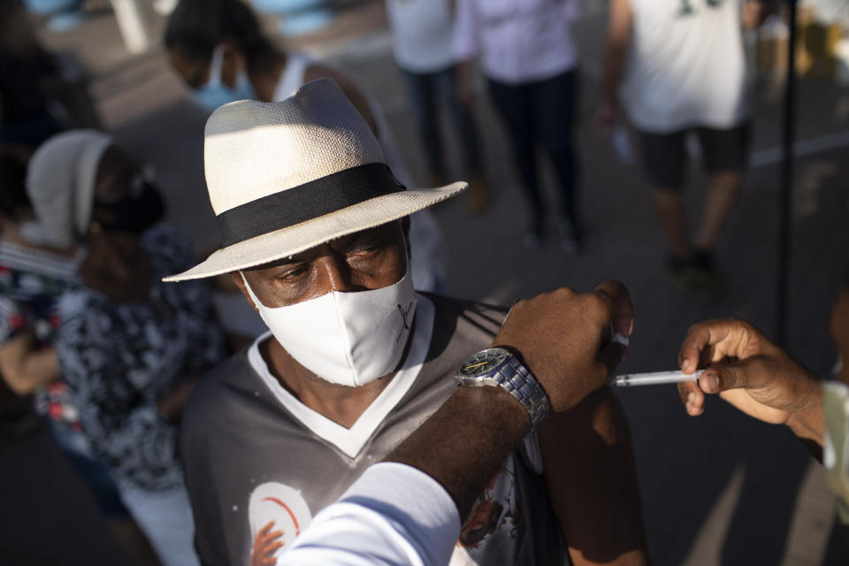 A man gets his dose of the Sinovac vaccine at a COVID-19 vaccination point for seniors in Duque de Caxias, Brazil, Wednesday, March 24, 2021. (AP Photo/Silvia Izquierdo)