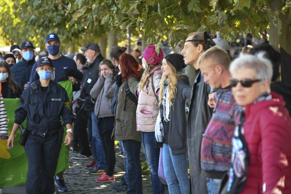 People form a so-called peace human chain, which is supposed to lead through Germany, Austria, Liechtenstein and Switzerland around Lake Constance, while on the left, supporters of the Corona measures are walking past it. (Felix Kaestle/dpa via AP)