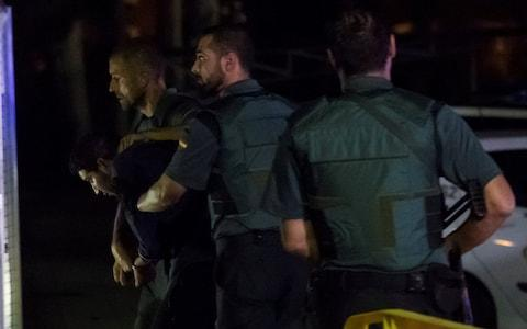 Spanish Civil Guards escort a man accused of involvement in an Islamist cell behind a van attack in Barcelona last week, in Tres Cantos - Credit: JUAN MEDINA/Reuters