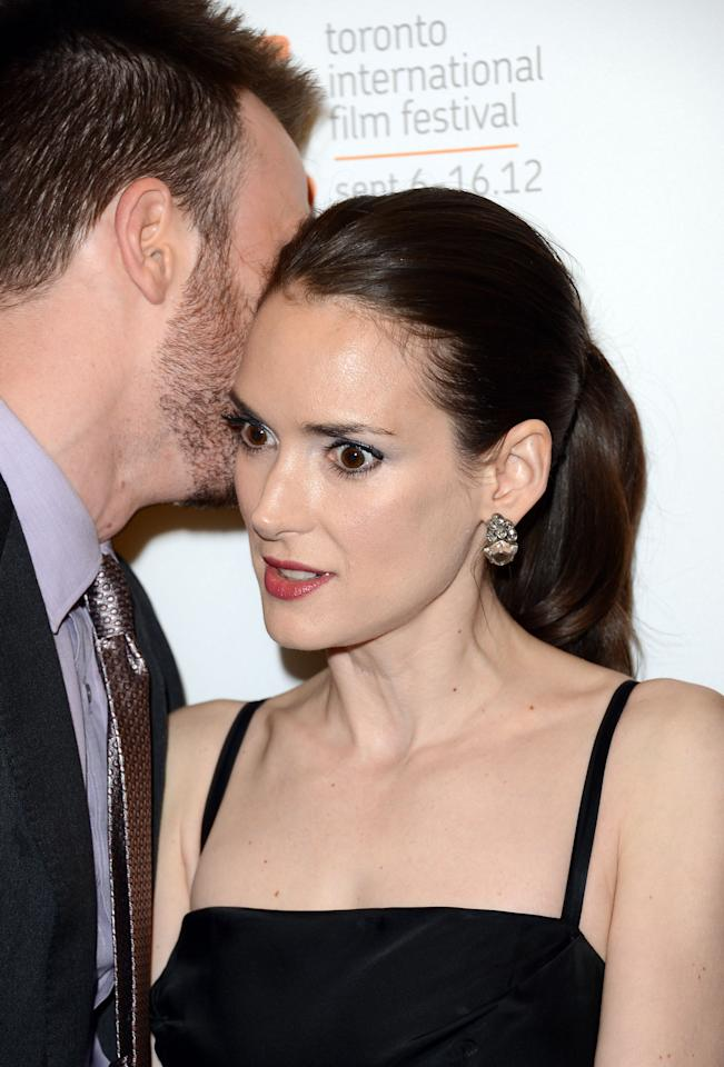 "Winona Ryder looks cold as ice as Chris Evans whispers what seems to be a not-so-sweet nothing into her ear on the red carpet of ""The Iceman."""