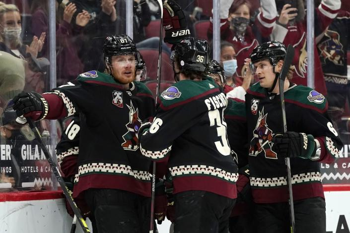 Arizona Coyotes left wing Lawson Crouse (67), Coyotes right wing Christian Fischer (36), and Coyotes defenseman Jakob Chychrun (6) celebrate a goal against the Los Angeles Kings by Coyotes' Christian Dvorak during the first period of an NHL hockey game Monday, May 3, 2021, in Glendale, Ariz. (AP Photo/Ross D. Franklin)