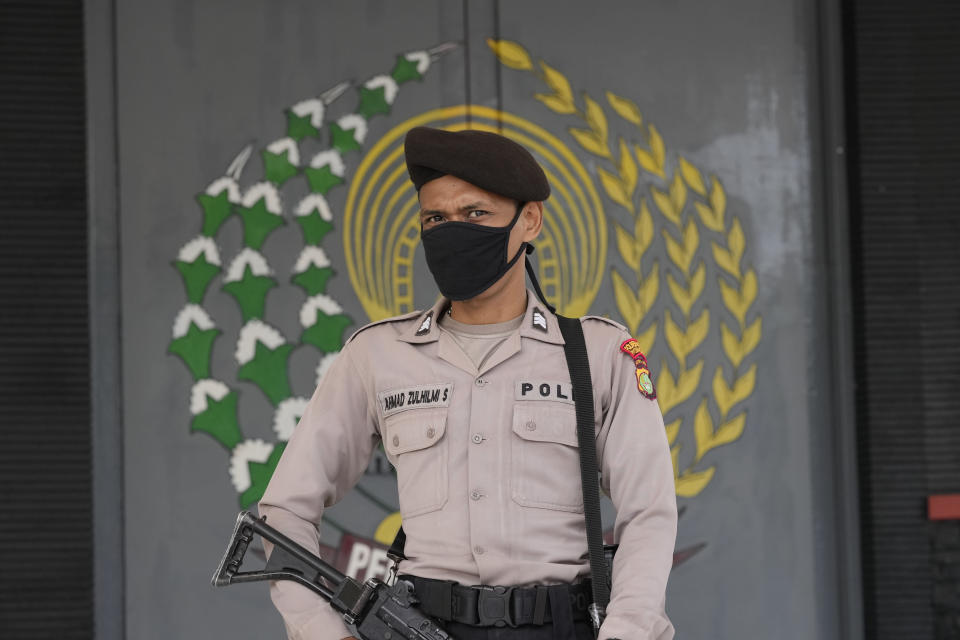 A police officers stands guard at the main entrance gate of Tangerang prison in Tangerang on the outskirts of Jakarta, Indonesia, Wednesday, Sept. 8, 2021. A massive fire raged through the overcrowded prison early Wednesday, killing a number of inmates. (AP Photo/Dita Alangkara)