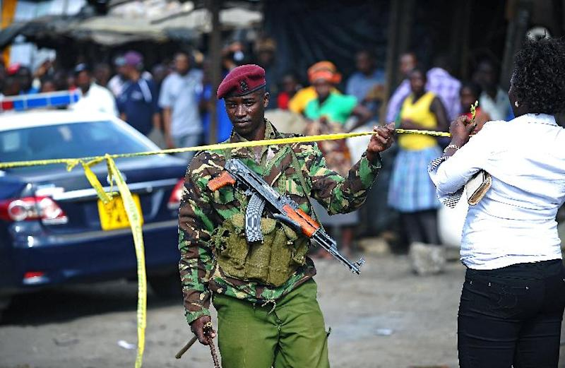 A Kenyan policeman stands at the scene of an explosion in Gikomba on the outskirts of Nairobi's business district where deadly twin blasts struck on May 16, 2014 (AFP Photo/John Muchucha)