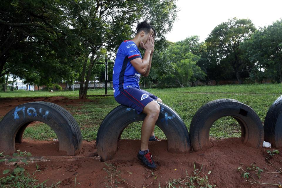 """Defender Jose """"Ruli"""" Rios, of the Fulgencio Yegros Club, second division, rubs his temples during a solitary, early morning training session in Ypane, Paraguay, Saturday, Jan. 30, 2021. A professional since age 18, the 35-year-old defender helped four clubs reach Paraguay's first division. To survive during during the COVID-19 pandemic, Rios is working as a gardener as he waits for the 2021 season to begin. (AP Photo/Jorge Saenz)"""