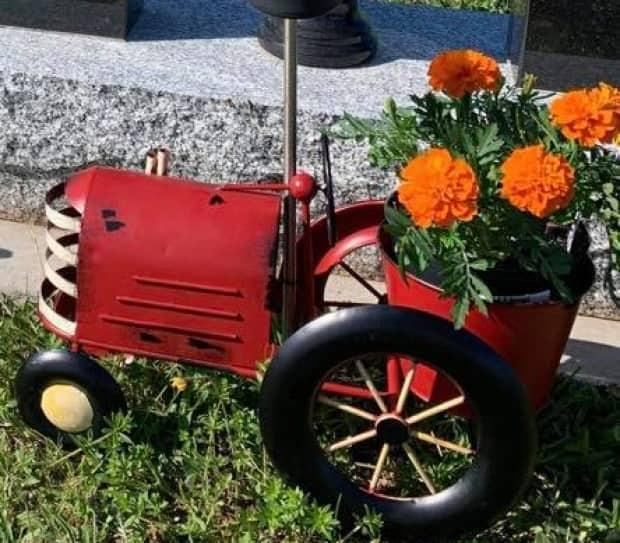 This small red tractor flower pot is missing from a grave in Mount Carmel. (Danielle Gallant - image credit)