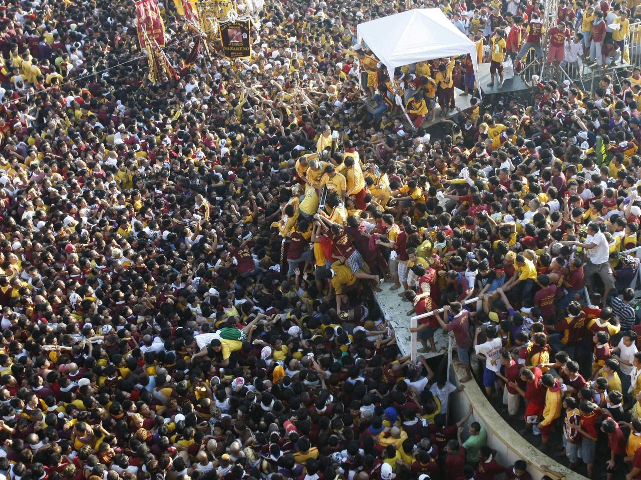 Barefoot Catholic devotees jostle to kiss the cross being borne by the wooden statue of the Black Nazarene, center, as they gather at the Rizal Park Monday, Jan. 9, 2012 during it's annual festival in Manila, Philippines. More than 3 million devotees paraded the charred Christ statue, believed to have healing powers, through the Philippine capital despite a warning from President Benigno Aquino III that terrorists might target the gathering. (AP Photo/Bullit Marquez)