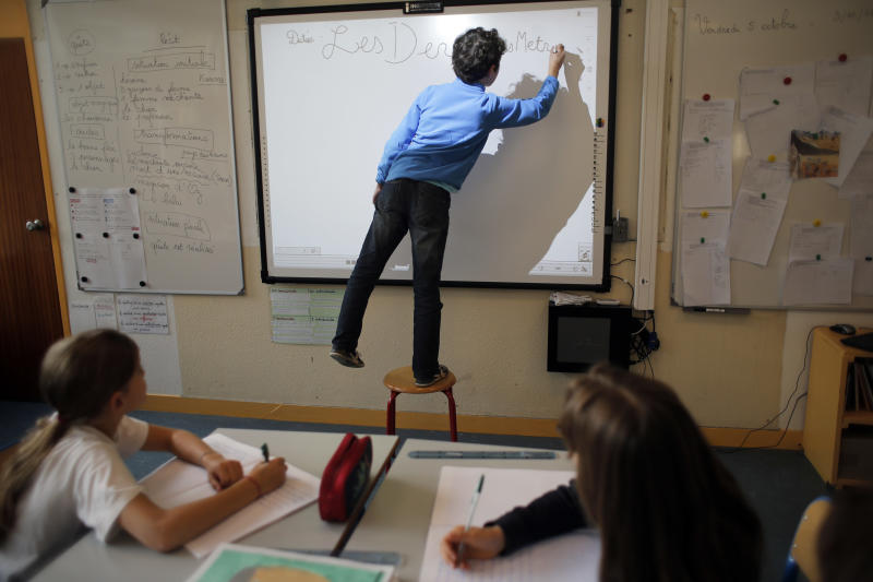 A student writes on the board at the school of La Ronce in Ville d'Avray, west of Paris, Friday, Oct. 5, 2012. French children go to school four days a week with about two hours each day for lunch. And they have more vacation than their counterparts almost anywhere in the West. As a candidate, President Francois Hollande promised to change things by adding a fifth day of classes on Wednesday while shortening the school day and education minister, Vincent Peillon, will decide this month how to carry out the reform. (AP Photo/Christophe Ena)