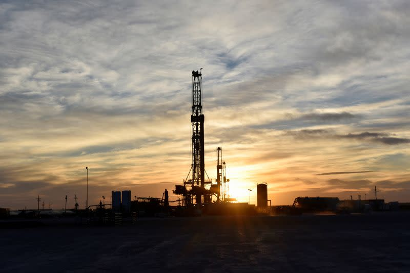 FILE PHOTO: Drilling rigs operate at sunset in Midland
