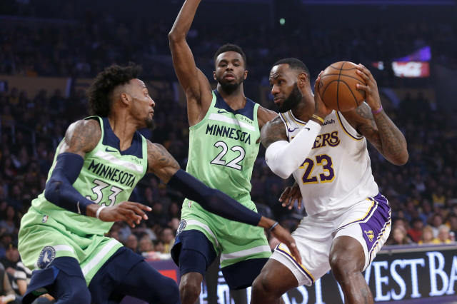 Los Angeles Lakers' LeBron James (23) is defended by Minnesota Timberwolves' Robert Covington (33) and Andrew Wiggins (22) during the first half of an NBA basketball game, Sunday, Dec. 8, 2019, in Los Angeles. (AP Photo/Ringo H.W. Chiu)