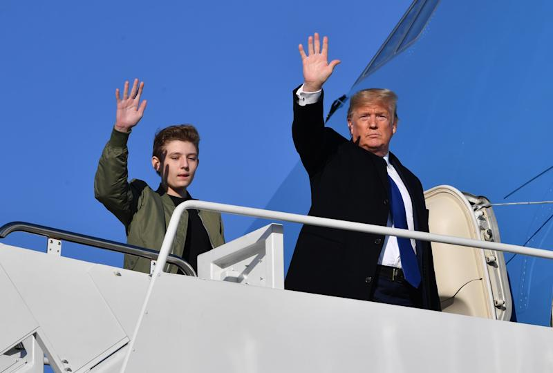 US President Donald Trump and son Barron Trump wave while making their way to board Air Force One at Andrews Airforce Base, Maryland on January 17, 2020. - Trump is traveling to Palm Beach, Florida.