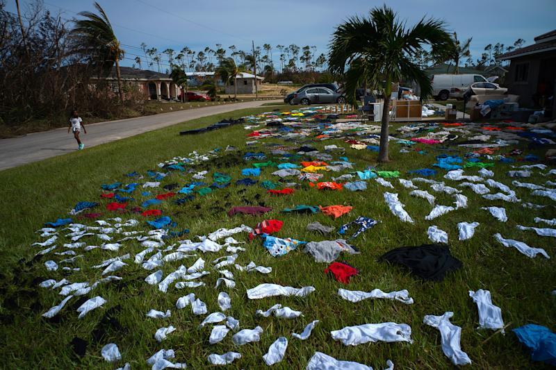 A child walks past clothes laid out to dry on a field in the aftermath of Hurricane Dorian in the Arden Forest neighborhood of Freeport, Bahamas, Sept. 4, 2019. | Ramon Espinosa—AP