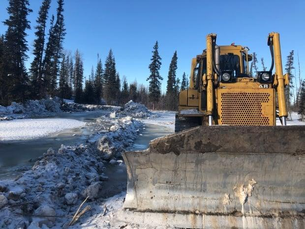 A construction vehicle sits at the site of an overflow on the Mackenzie Valley winter road in March 2019. (John Last/CBC - image credit)