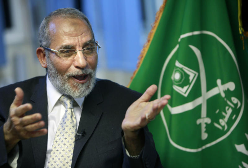 "The Muslim Brotherhood General Guide Mohammed Badie talks during an interview with the Associated Press at his office in Cairo Egypt, late, Tuesday, Oct. 26, 2010. The Leader of Egypt's biggest Islamic opposition movement accused President Hosni Mubarak's ruling regime of trying to ""take over elections and power exclusively and forever,'' through fraud and saying that the lack of Mubarak's party's popularity is the reason behind rigging the vote. At right is the logo of The Muslim Brotherhood.(AP Photo/Amr Nabil)"