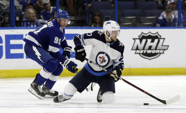 Winnipeg Jets left wing Nikolaj Ehlers (27) plays the puck from his knees after getting taken down by Tampa Bay Lightning center Steven Stamkos (91) during the second period of an NHL hockey game Tuesday, March 5, 2019, in Tampa, Fla. (AP Photo/Chris O'Meara)