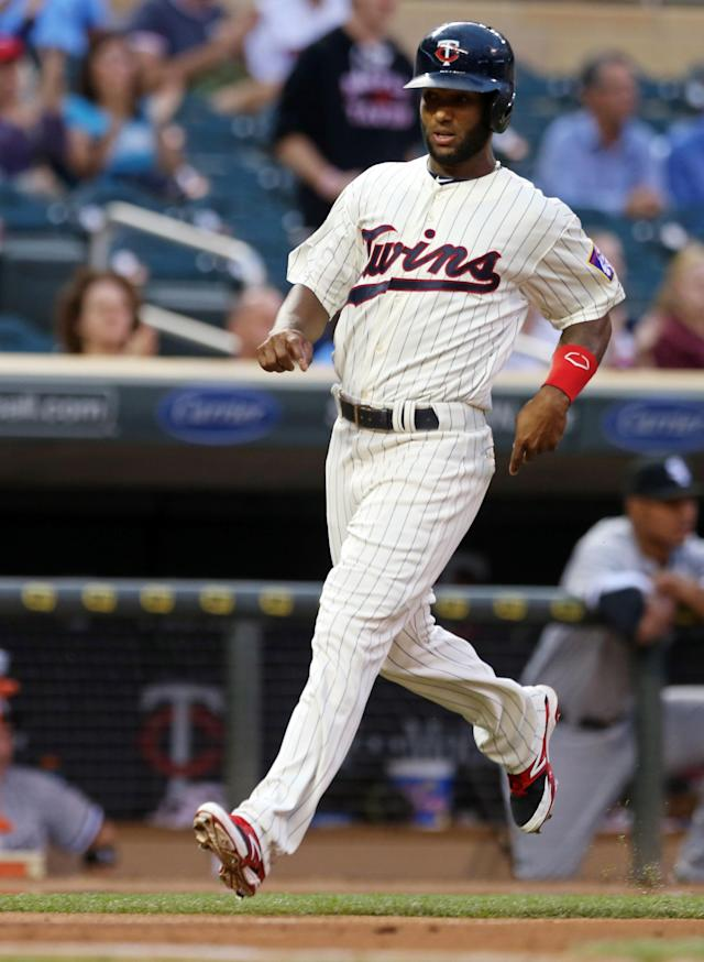 Minnesota Twins' Danny Santana scores on a triple by Eduardo Nunez off Chicago White Sox pitcher John Danks in the first inning of a baseball game, Wednesday, Sept. 3, 2014, in Minneapolis. (AP Photo/Jim Mone)