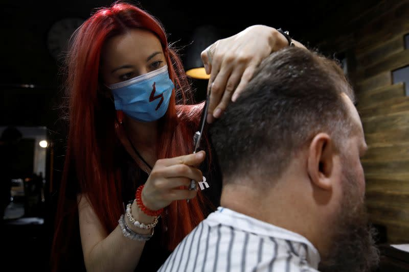 Barber Kinga Rutkowska, 22, cuts hair at a barbershop in Warsaw