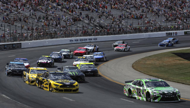 Kyle Busch (18) pulls ahead of pole sitter Brad Keselowski (2) during a NASCAR Cup Series auto race at New Hampshire Motor Speedway in Loudon, N.H., Sunday, July 21, 2019. (AP Photo/Charles Krupa)