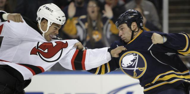 FILE - In this Oct. 13, 2010, file photo, Buffalo Sabres' Cody McCormick, right, fights with New Jersey Devils' Mark Fraser during the first period of an NHL hockey game in Buffalo, N.Y. Fighting has been a part of the NHL for about as long as the sport has existed. The NHL has toughened penalties and imposed longer suspensions for cheap shots, undercutting the players' unwritten code of justice. (AP Photo/David Duprey, File)