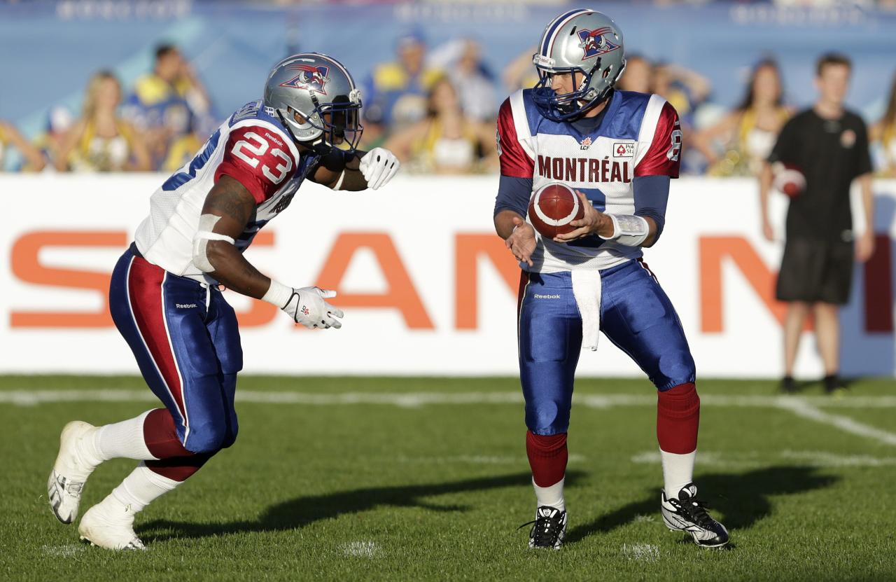Montreal Alouettes quarterback Josh Neiswander (R) hands off the football to running back Jerome Messam during the first half of the 2013 CFL Touchdown Atlantic game against the Hamilton Tiger-Cats in Moncton, New Brunchwick, September 21, 2013. REUTERS/Devaan Ingraham (CANADA - Tags: SPORT FOOTBALL)