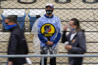 Fans walks past a track ambassador urging fans to wear masks as rain delayed the start of the final practice session for the Indianapolis 500 auto race at Indianapolis Motor Speedway in Indianapolis, Friday, May 28, 2021. (AP Photo/Michael Conroy)