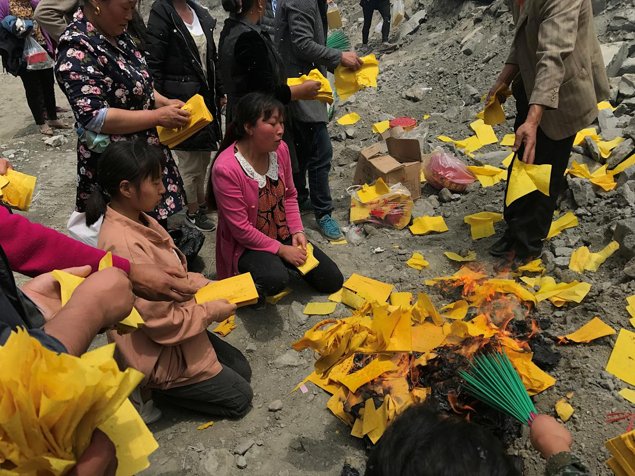 <p>Relatives of victims burn incense and paper money to mourn their dead relatives at the site of a landslide in the village of Xinmo, Mao County, Sichuan Province, China, June 26, 2017. (Photo: Aly Song/Reuters) </p>
