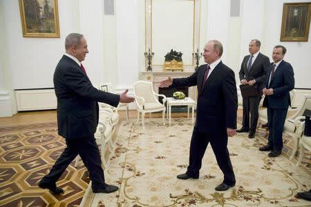 Russian President Vladimir Putin (R) approaches to shake hands with Israeli Prime Minister Benjamin Netanyahu during a meeting in Moscow, Russia, March 9, 2017. REUTERS/Pavel Golovkin/Pool
