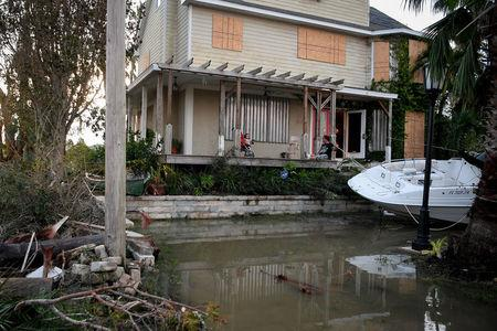 Residents sit on their front porch watching water reside after Hurricane Irma in Everglades City, Florida, U.S., September 11, 2017. REUTERS/Bryan Woolston