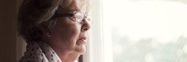 older woman wearing a robe and glasses and looking out the window
