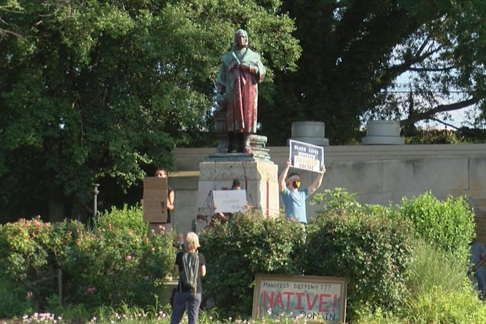 Protesters gather in front of a statue of Christopher Columbus in Richmond, Va.