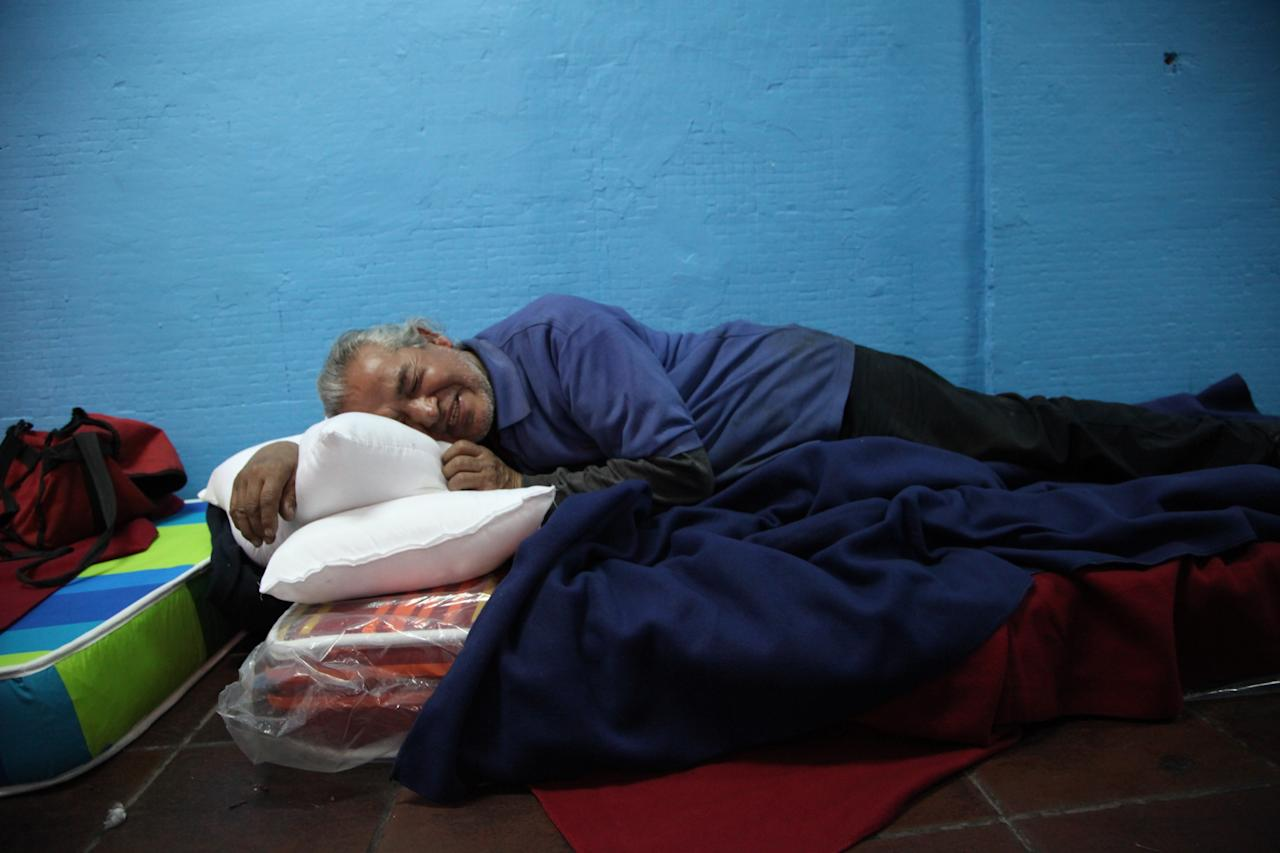 In this May 20, 2013 photo, Armando Patricio Galleguillos Luna, 63, lies on a mattress in the designated area for people who have been using a substance, before they can access the rest of the shelter at the indoor stadium Estadio Victor Jara in Santiago, Chile. A census for the homeless shows that 12,225 people were living on the street last year. (AP Photo/Brittany Peterson)