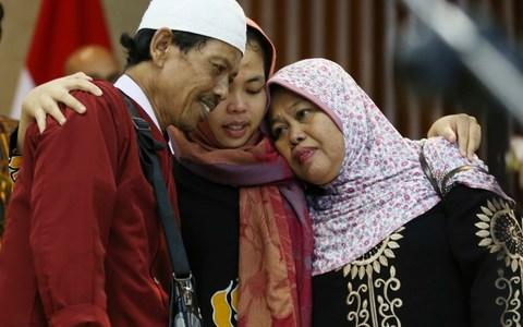 Siti Aisyah hugs here relieved father, Asria, and mother, Binah - Credit: Achmad Ibrahim/AP