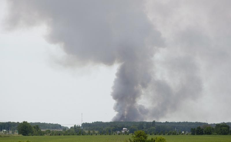 Smoke billows from the B.E.M fireworks factory following an explosion in Coteau du Lac, Que., Thursday, June 20, 2013. Quebec provincial police are investigating a massive explosion at a fireworks factory west of Montreal. There were no immediate reports of injuries and the cause of the blast is unknown. Police have ordered the surrounding community of Coteau-du-Lac evacuated. (AP Photo/The Canadian Press, Graham Hughes)