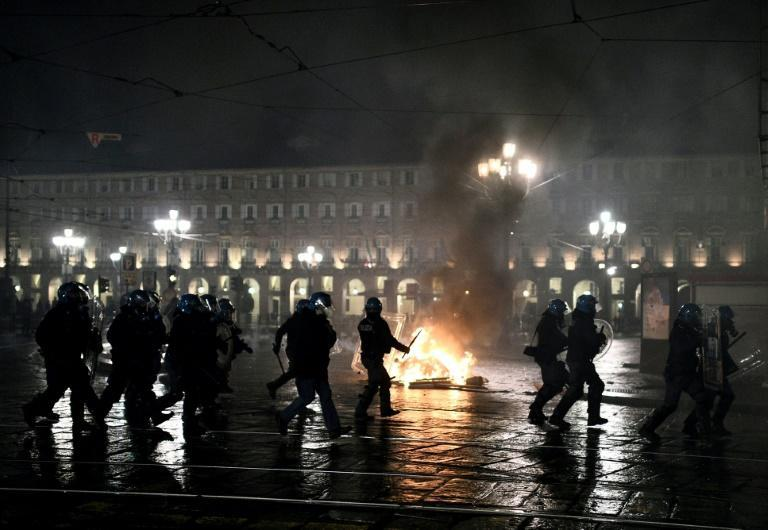 Italian police officers stand in front of a wheelie-bin on fire during a protest in downtown Turin.