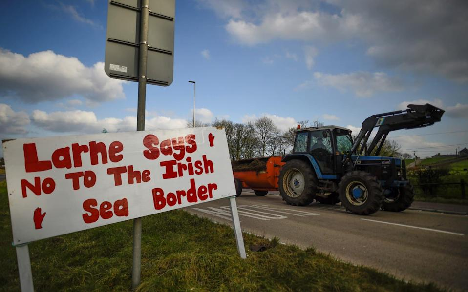 A sign against the Brexit border checks in relation to the Northern Ireland protocol at the harbour in Larne - CLODAGH KILCOYNE/REUTERS