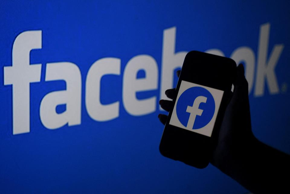 A smart phone screen displays the logo of Facebook on a Facebook website background (AFP via Getty Images)