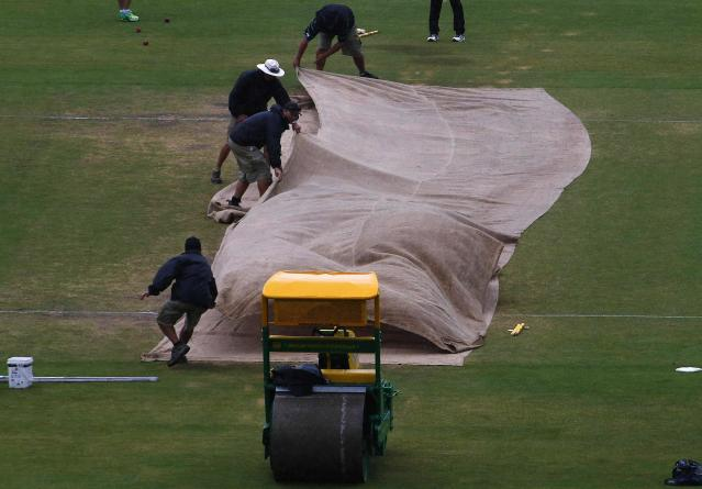 Grounds workers cover the pitch as the start of the match was delayed due to rain during the fifth day's play in the second Ashes cricket test between England and Australia at the Adelaide Oval December 9, 2013. REUTERS/David Gray (AUSTRALIA - Tags: SPORT CRICKET)