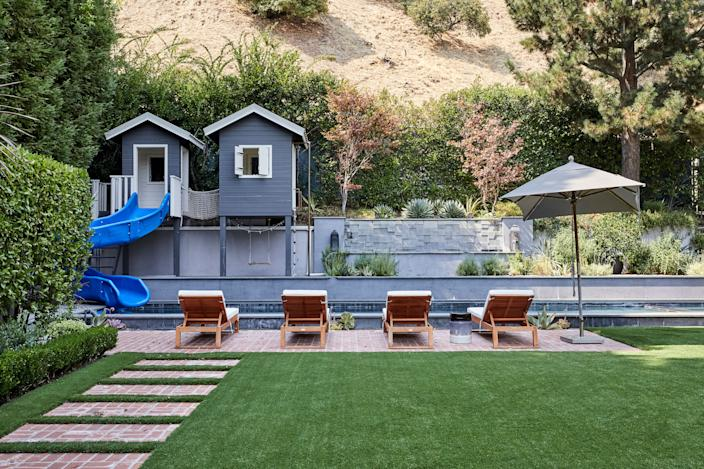 """<div class=""""caption""""> Gray tiles, a water feature, and an incredible kids' clubhouse complete with water slide—by <a href=""""https://www.cwilliamsconstruction.com/"""" rel=""""nofollow noopener"""" target=""""_blank"""" data-ylk=""""slk:Craig Williams Construction"""" class=""""link rapid-noclick-resp"""">Craig Williams Construction</a>—were all added to the home's original pool area. """"My son is more interested in jumping off the side, which gives me a heart attack,"""" says Duff. """"But the kids go crazy for it."""" As for the landscaping, Duff adds, """"I dream of changing the brick path in the lawn—that was an O.G., original of the house—but I think it bothers me way more than it bothers other people. I will have conversations about it and they're always like, 'Wait, what's wrong with it?'"""" </div>"""