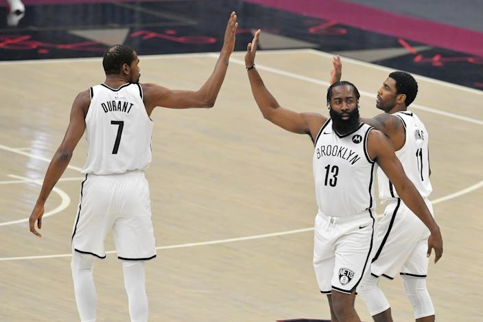 CLEVELAND, OHIO - JANUARY 20: Kevin Durant #7  James Harden #13 and Kyrie Irving #11 of the Brooklyn Nets celebrate during the first quarter against the Cleveland Cavaliers at Rocket Mortgage Fieldhouse on January 20, 2021 in Cleveland, Ohio. NOTE TO USER: User expressly acknowledges and agrees that, by downloading and/or using this photograph, user is consenting to the terms and conditions of the Getty Images License Agreement. (Photo by Jason Miller/Getty Images)