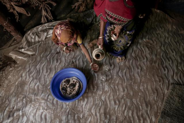 <p>Hagar Yahia pours tea for her 5-year-old daughter Awsaf in their hut in Abyan, Yemen in this Feb. 15, 2018 photo. Many families across southern Yemen described how they live largely on bread and sweetened tea, sometimes just once a day. (Photo: Nariman El-Mofty/AP) </p>