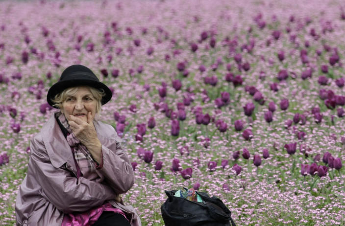 """An elderly woman watches members of anti-war organization """"Women in Black"""", unseen, during the organization's anti-war protest in downtown Belgrade, Serbia, Friday, April 6, 2012. Sarajevo on Friday marks the 20th anniversary of the start of the Bosnian war. Exhibitions, concerts and performances are being held, but nothing can match the impact of hundreds of rows of red in the same square where it all started on April 6, 1992. (AP Photo/Darko Vojinovic)"""