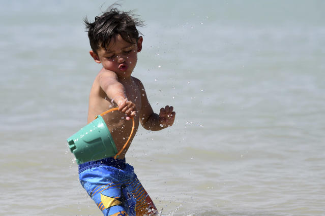 <p>Urijah Salcedo throws a bucket of water on himself while playing in Spring Valley Lake in Victorville Calif., June 19, 2017. (James Quigg/The Daily Press via AP) </p>