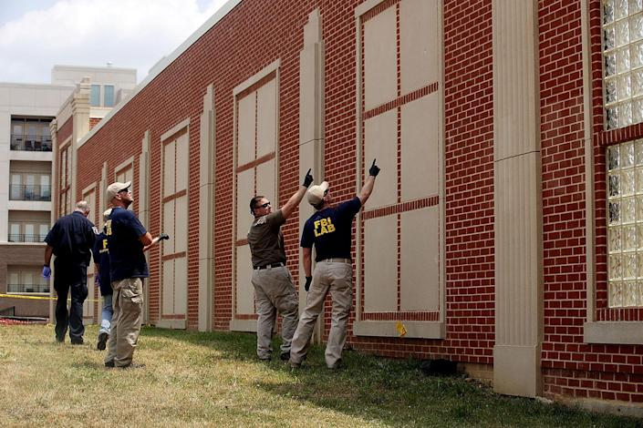 <p>Members the FBI survey the damages possibly caused by gun shots on a wall at the site of this morning's shooting at Eugene Simpson Stadium Park, June 14, 2017 in Alexandria, Va. (Photo: Alex Wong/Getty Images) </p>
