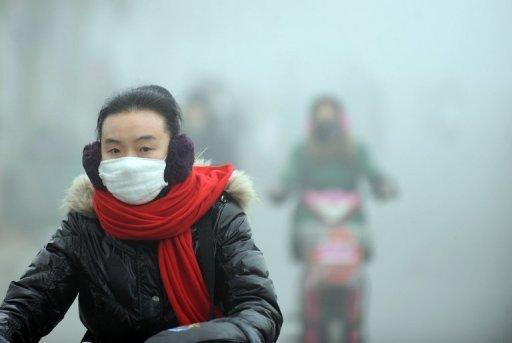 <p>A woman rides a bike in heavy smog in Haozhou, central China's Anhui province on January 30, 2013. The suffocating smog that blanketed swathes of China is now hitting parts of Japan, sparking warnings of health risks for the young and the sick.</p>
