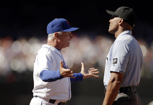 New York Mets manager Terry Collins, left, argues against first base umpire CB Bucknor 's fourth inning call in a baseball game against the Milwaukee Brewers, Sunday, Sept. 29, 2013, in New York. Bucknor ruled Brewers Sean Halton safe at first on a fielder's choice but both Collins and Mets starting pitcher Jonathon Niese thought Halton was out on the play. (AP Photo/Kathy Willens)