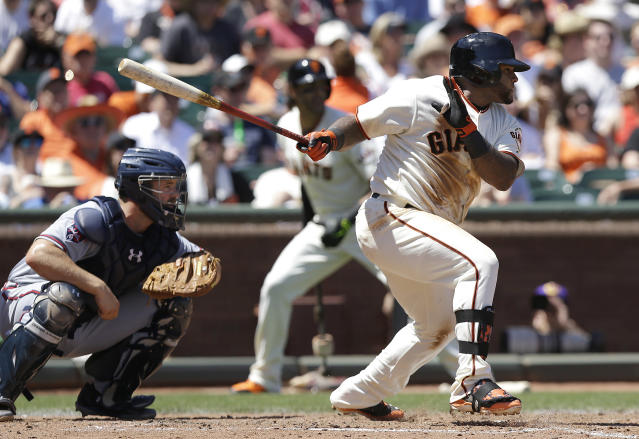 San Francisco Giants' Pablo Sandoval follows through on a single that scored Hunter Pence, next to Atlanta Braves catcher Evan Gattis during the fourth inning of a baseball game in San Francisco, Wednesday, May 14, 2014. (AP Photo)