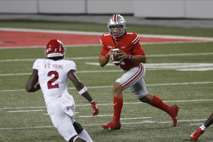 Ohio State quarterback Justin Fields, right, looks for an open receiver as Rutgers defensive back Avery Young defends during the first half of an NCAA college football game Saturday, Nov. 7, 2020, in Columbus, Ohio. (AP Photo/Jay LaPrete)