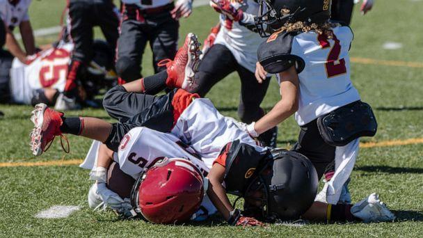 PHOTO: A youth football player is tackled and at bottom of a pile during a game. (Jon Osumi/Shutterstock)